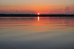 Soluppgång med reflexion i lugna vatten Royaltyfria Bilder