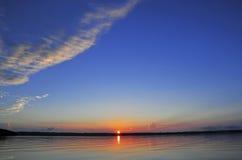 Soluppgång med reflexion i lugna vatten Arkivfoton