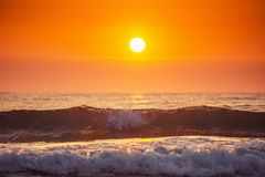 Soluppgång och att skina vinkar i havet Arkivfoto