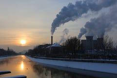Soluppgång och rök från fabrikslampglas i vinter Arkivbild