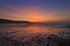 Soluppgång reflekterade i den våta sanden och kiselstenarna av den sötvattens- östliga stranden Arkivfoto