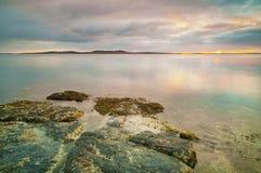 Soluppgång över ett lugna hav Royaltyfria Bilder