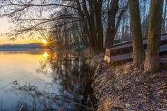 Soluppgång över sjön på slutet av vintern Arkivbild
