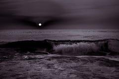 Soluppgångsolnedgång över havshavvågorna i svartvitt Arkivbilder
