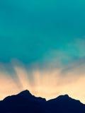Soluppsättning bak bergmaxima i fjällängarna av Schweiz Royaltyfria Bilder