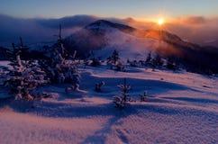 Soluppsättning i berg med vinter- och förkylninglandskap Royaltyfri Fotografi