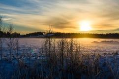 Soluppsättningar på ett vintrigt lantgård- och skoglandskap Royaltyfri Foto