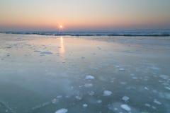 Soluppsättningen över den djupfrysta sjön Royaltyfri Fotografi