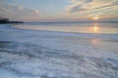 Soluppsättningen över den djupfrysta sjön Royaltyfri Foto