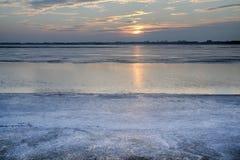 Soluppsättningen över den djupfrysta sjön Royaltyfria Foton