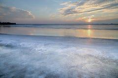 Soluppsättningen över den djupfrysta sjön royaltyfri bild