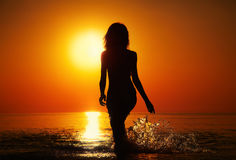 Solute into sunset. Silhouette of a girl in the water at sunset. Natural light and dark. Artistic colors added. Horizontal photo Stock Photo