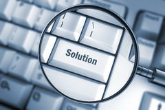 Solution. The word solution printed on the keyboard that can be seen via a magnifier with a blur background. A blue toned image Royalty Free Stock Photos