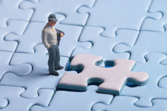 Solution. Plastic figure standing in front of a puzzle piece, a man (figure) has to make decisions, whether this is the right solution Royalty Free Stock Photography