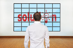 Solution. Businessman looking at solution on plasma in office Royalty Free Stock Image