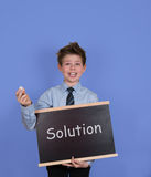 Solution concept. Boy with chalkboard slate on blue background. Solutions written with white chalk on a blackboard royalty free stock photos