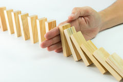 Solution. Concept with hand stopping wooden blocks from falling in the line of domino stock images