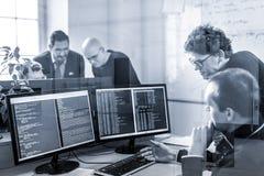 Solution de problème commercial de jeune entreprise Programmateurs de logiciel travaillant sur l'ordinateur de bureau Image stock