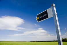 Solution direction sign. Direction sign showing solution against blue sky stock photography