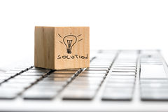 Solution and a hand-drawn illuminated light bulb. Innovation concept with the word Solution and a hand-drawn illuminated light bulb on a wooden block lying on a Stock Photography
