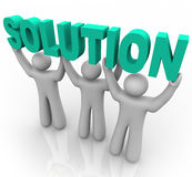 Solution - Lifting the Word. Three people join forces to lift the word Solution Royalty Free Stock Photo