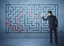 Solution of a maze. Businessman finding the solution of a maze Stock Photos
