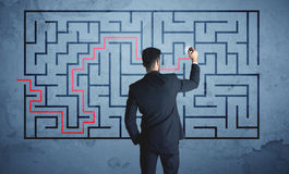 Solution of a maze. Businessman finding the solution of a maze Stock Photo