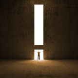 Solution metaphor. Man stands in the light. Of exclamation mark shaped opening Royalty Free Stock Photography