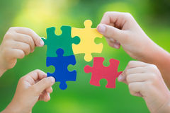 Solution. Multicolor puzzles in hands against green spring blurred background. Teamwork and solution concept Royalty Free Stock Photography