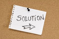 Solution note on pinboard. Word SOLUTION written on paper sheet on corkboard Stock Photo