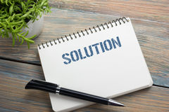 Solution. Notepad with message, pen and flower. Office supplies on desk table top view Stock Image