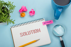 Solution. Notepad with message, pencil, coffee cup and flower. Office supplies on desk table top view. Solution. Notepad with message, pencil, coffee cup and Stock Photos