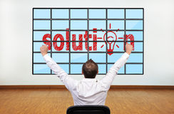 Solution on plasma. Happy businessman looking at solution on plasma in office Royalty Free Stock Image