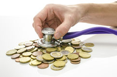 Solution to financial crisis concept. Male hand with stethoscope on Euro coins Stock Photo
