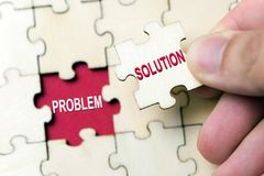 Solution to problem concept. Hand holding piece of jigsaw puzzle with word problem and solution Royalty Free Stock Photography