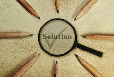 Solution. Word Solution under a magnifying glass on vintage background Royalty Free Stock Photography