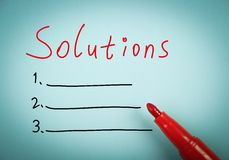 Solutions. Concept is on blue paper with a red marker aside Stock Photography