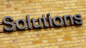 Solutions Sign. Sign with the word solutions in black letters hanging against a brick wall Stock Photography