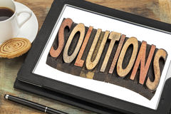 Solutions word abstract in on digital tablet. Solutions word abstract - text in vintage letterpress  wood type printing blocks on a digital tablet with cup of Stock Image