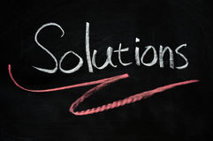 Solutions written on blackboard Stock Photos