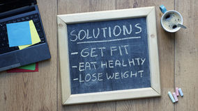 Solutions written. Solutions get, fit, eat healthy and lose weight written on a chalkboard at the office Royalty Free Stock Photography