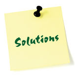 Solutions, written on a sticky adhesive note, isolated yellow post-it style sticker, black thumbtack pushpin, green text Stock Photography