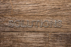 Solutions written on wooden background Royalty Free Stock Photo