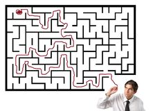 Solve a difficult situation. Portrait of a young businessman solving a difficult labyrinth maze Stock Photos