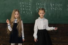 Solve problem. two schoolgirls solve problem at school. solve problem at school lesson. helping each other to solve Stock Photo
