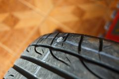 Tires leak because the screw nail pounding,replacement repair fixing car`s tire trying to remove nail from hole. Flat tire. punctu. Solve problem wheel in garage Royalty Free Stock Images