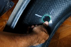 Solve problem wheel in garage auto repair shop service. replacement repairman fixing car`s tire trying to remove nail from hole. F. Lat tire. Accident with stock image