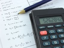 Solving. Mathematical equations with a pencil and calculator royalty free stock images