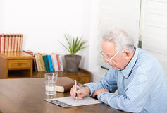 Solving ceosswords. Senior man in pajamas with reading glasses sitting at table and solving crosswords stock images