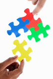 Solving colorful puzzle Stock Photos